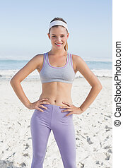 Sporty blonde on the beach smiling