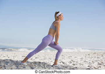 Sporty blonde on the beach stretchi