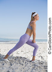 Sporty blonde on the beach stretching
