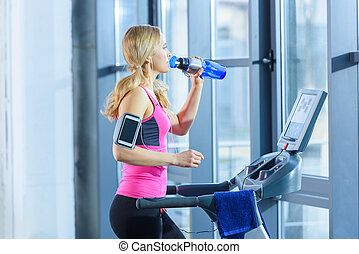 Sporty blonde woman exercising on treadmill and drinking water