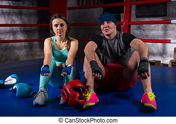 Sporty boxing couple sitting near lying boxing gloves and helmet