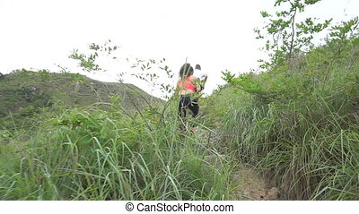 Sporty boy and girl running on difficult high mountain track. Woman and man work out in nature