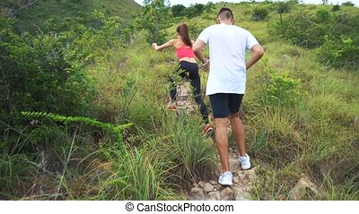 Sporty boy and girl running on mountain track. Woman and man work out in nature