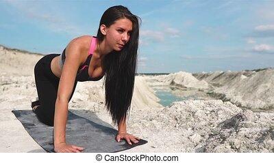 Sporty brunette girl in black sportswear trains against a...