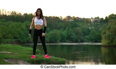 Sporty brunette in a white top black tight pants and pink...