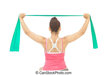 Sporty brunette stretching with resistance band on white...