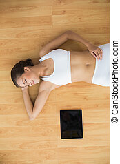 Sporty brunette with closed eyes lying next to a tablet
