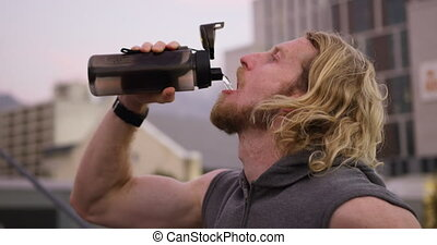 Sporty Caucasian man drinking water - A young athletic ...