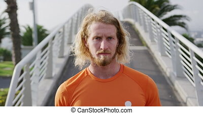 Sporty Caucasian man on a bridge