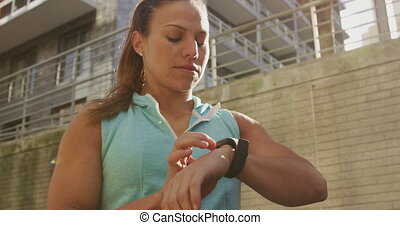 Sporty Caucasian woman checking her smartwatch outdoor - A ...