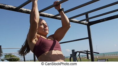 A sporty Caucasian woman with long dark hair exercising in an outdoor gym during daytime, pulling up an exercising frame, in slow motion.