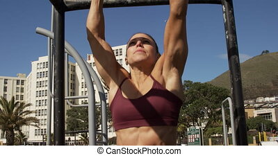 A sporty Caucasian woman with long dark hair exercising in an outdoor gym during daytime, hanging off an exercising frame, in slow motion.