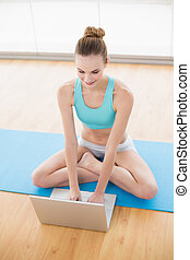 Sporty cheerful woman using laptop
