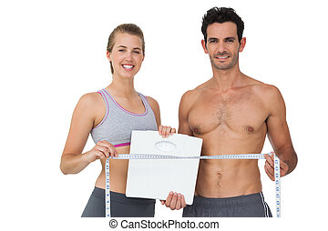 Sporty couple holding scales and measuring tape - Portrait ...