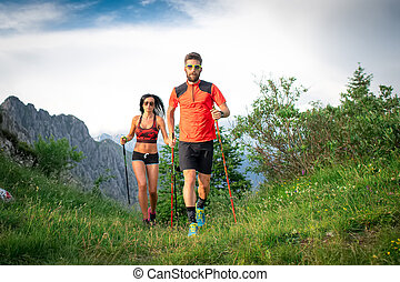 Sporty couple in the mountains with nordic walking poles