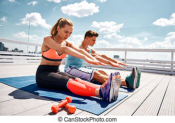 Sporty couple is concentrated on flexibility workout outdoors