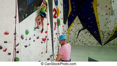 Sporty couple of climbers dressed in rock climbing outfit training at bouldering gym