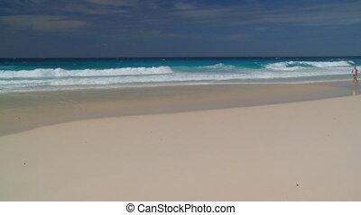 sporty couple running on sandy beach