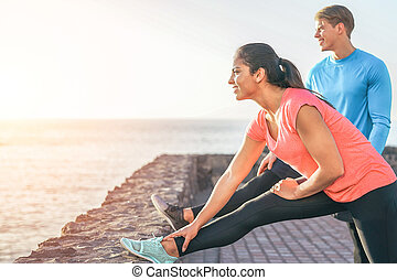 Sporty couple stretching legs in front of ocean at sunset - young people training and making legs exercises outdoor - Sport, relationship, healthy lifestyle concept