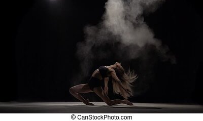 Sporty dancer throwing dust particles in air. Slow motion
