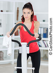 sporty determined young woman training on step machine
