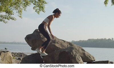 Active attractive black female athlete climbing rocks on river bank, relaxing and enjoying beautiful natural landscape in rays of warm summer sunrise after workout, expressing positivity and happiness