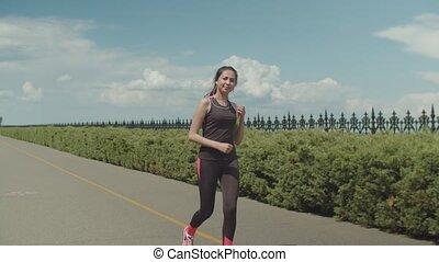 Sporty female runner meeting friend in city park