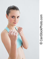 Sporty fit woman clenching fists against wall