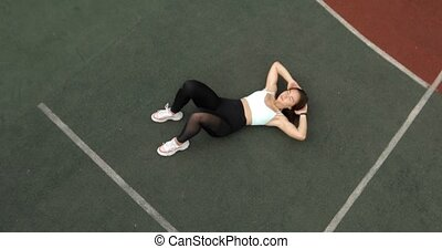 Sporty fit woman is doing abs exercises crunches on sport ground on stadium.