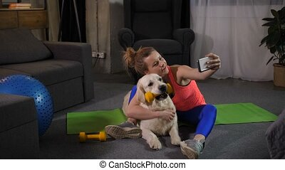 Sporty fit woman making selfie shot with pet dog - Cheerful...