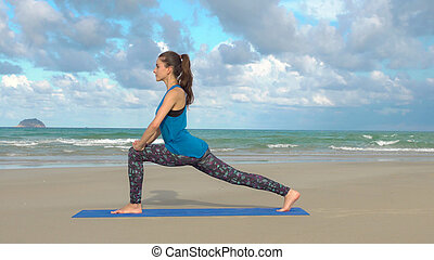 Sporty fit woman practicing yoga on the beach at sunset. Healthy lifestyle.