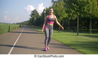 Sporty fit woman walking in park after workout