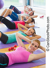 Sporty fitness class doing sit ups on exercise mats - ...