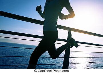 sporty fitness female runner running on seaside boardwalk...