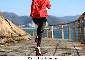 sporty fitness female runner running on seaside boardwalk