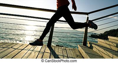 sporty fitness female runner running upstairs on coast trail
