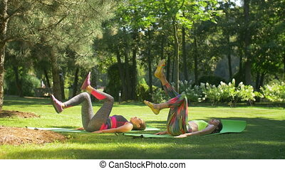 Sporty fitness females doing bicycle crunch in park -...