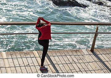 sporty fitness woman runner stretching legs on seaside boardwalk