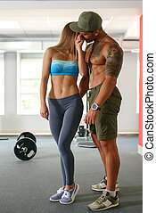 Sporty girl flirting with muscular man in gym
