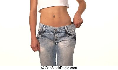 Sporty girl in big jeans, showing her lose weight, on white