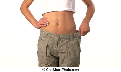 Sporty girl in big trousers, showing her lose weight, on white
