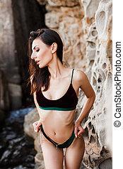 Sporty girl in bikini posing among rocks at sea.