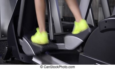 Sporty girl in sneakers pedals on the simulator. Close up.