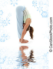 uttanasana standing forward bend on white sand - sporty girl...