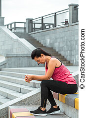 Sporty girl sitting on the stairs