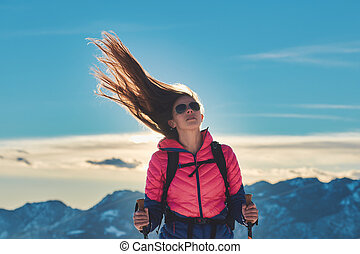 Sporty girl with hair blowing in the wind during mountain hike