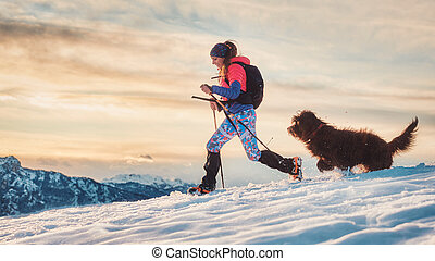 Sporty girl with her dog during an alpine trekking on the snow