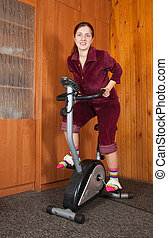 Sporty girl working out on exercycle