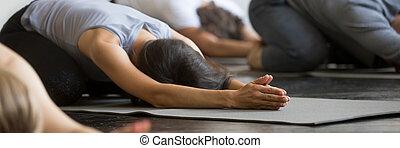 Sporty girls guys practicing Child exercise doing Balasana yoga pose