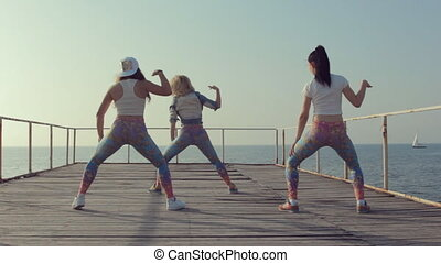 Sporty girls shaking their butts on the pier near the sea